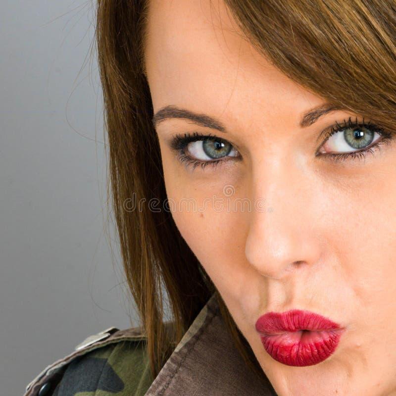 Giovane donna che soffia un bacio che sembra sensuale fotografie stock