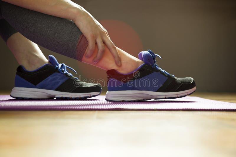 Giovane donna che soffre da una ferita alla caviglia mentre esercitandosi Spo fotografia stock libera da diritti