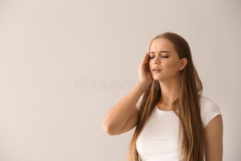 Giovane donna che soffre dall'emicrania su fondo leggero immagine stock libera da diritti