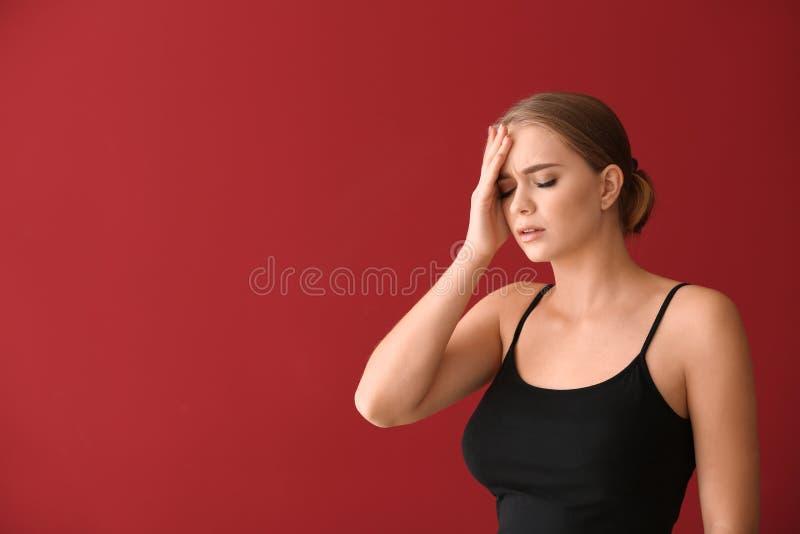 Giovane donna che soffre dall'emicrania sul fondo di colore immagini stock libere da diritti