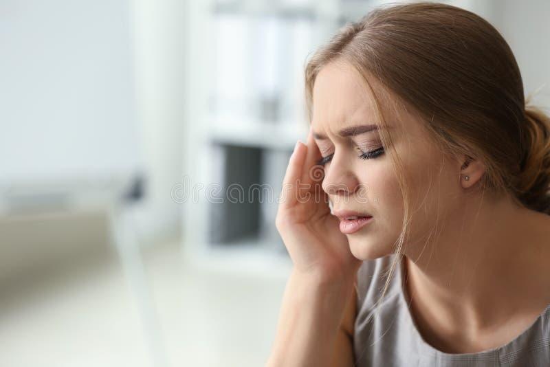 Giovane donna che soffre dall'emicrania in ufficio fotografia stock