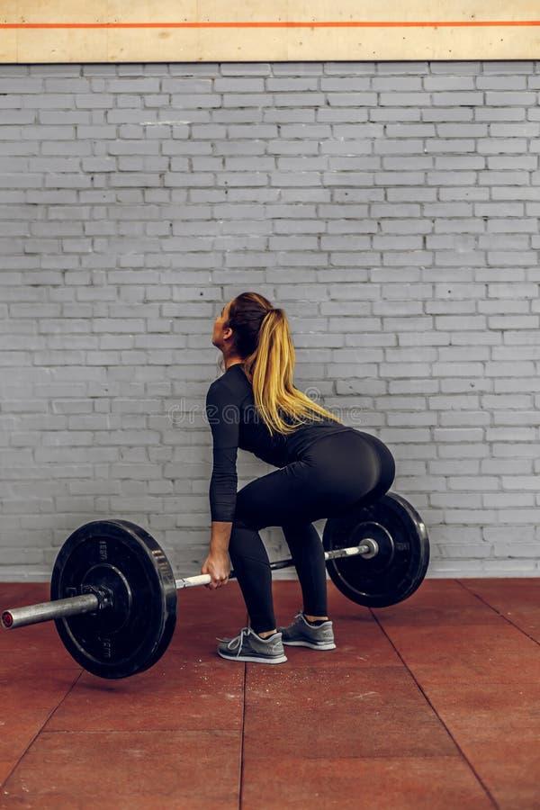 Giovane donna che solleva i pesi pesanti alla palestra fotografia stock
