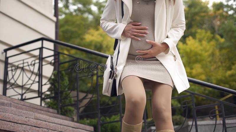 Giovane donna che sopporta dolore acuto improvviso di sensibilità del bambino all'aperto, contrazioni fotografia stock