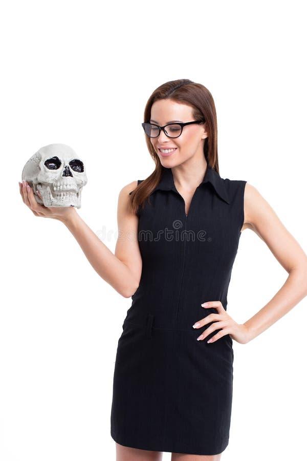 Giovane donna che sorride sul cranio isolato su bianco immagini stock