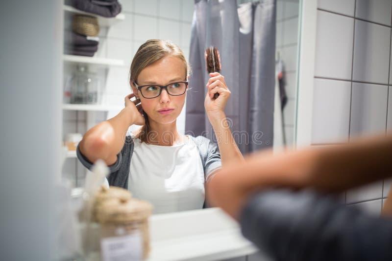 Giovane donna che spazzola capelli sani davanti ad uno specchio fotografie stock