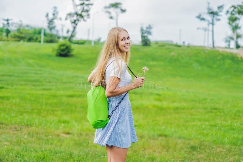 Giovane donna che sta con il sofà gonfiabile piegato nel parco lamzac fotografia stock
