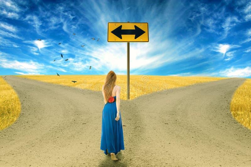 Giovane donna che sta davanti a due strade fotografie stock libere da diritti