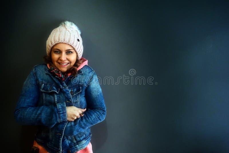 Giovane donna che sta e che sorride con il rivestimento immagini stock libere da diritti