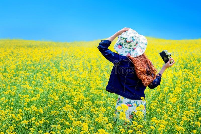 Giovane donna che sta nel giacimento giallo del seme di ravizzone immagini stock libere da diritti