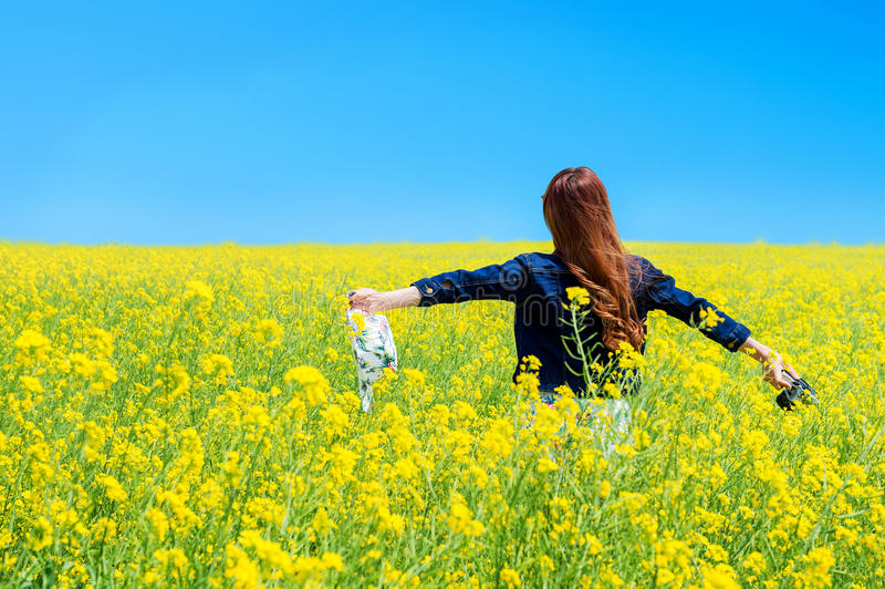 Giovane donna che sta nel giacimento giallo del seme di ravizzone fotografie stock libere da diritti