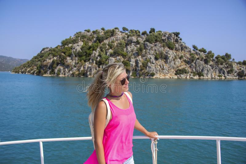 Giovane donna che sta sull'yacht al giorno soleggiato e che guarda ad un mare fotografia stock libera da diritti