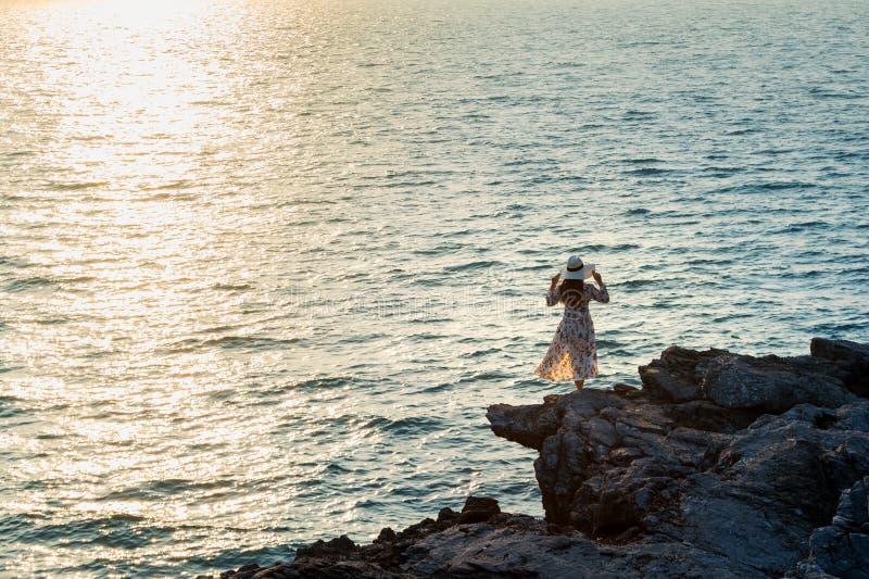 Giovane donna che sta sulla cima di roccia e che esamina la spiaggia ed il tramonto nell'isola di chang di si fotografie stock