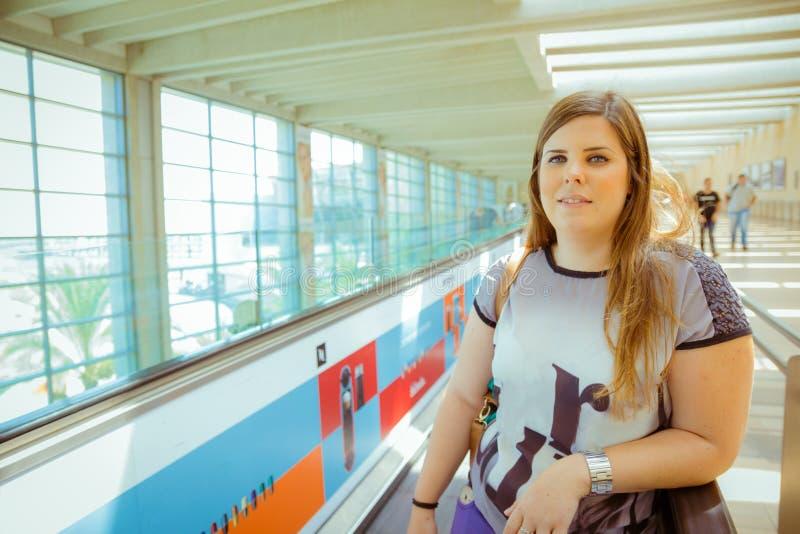 Giovane donna che sta sulla linea della scala mobile nel terminale di aeroporto e nella l immagine stock