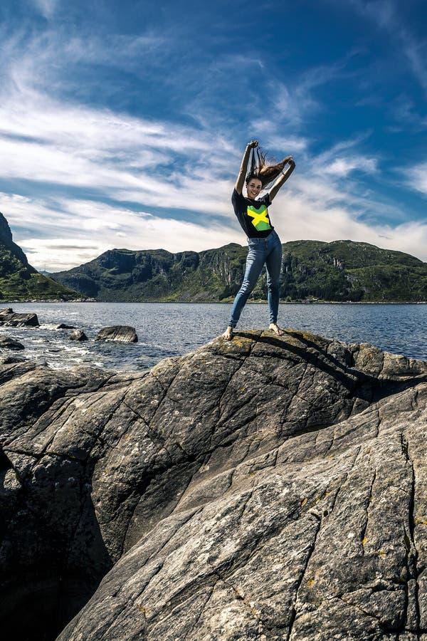 Giovane donna che sta sulle rocce, Norvegia fotografia stock libera da diritti