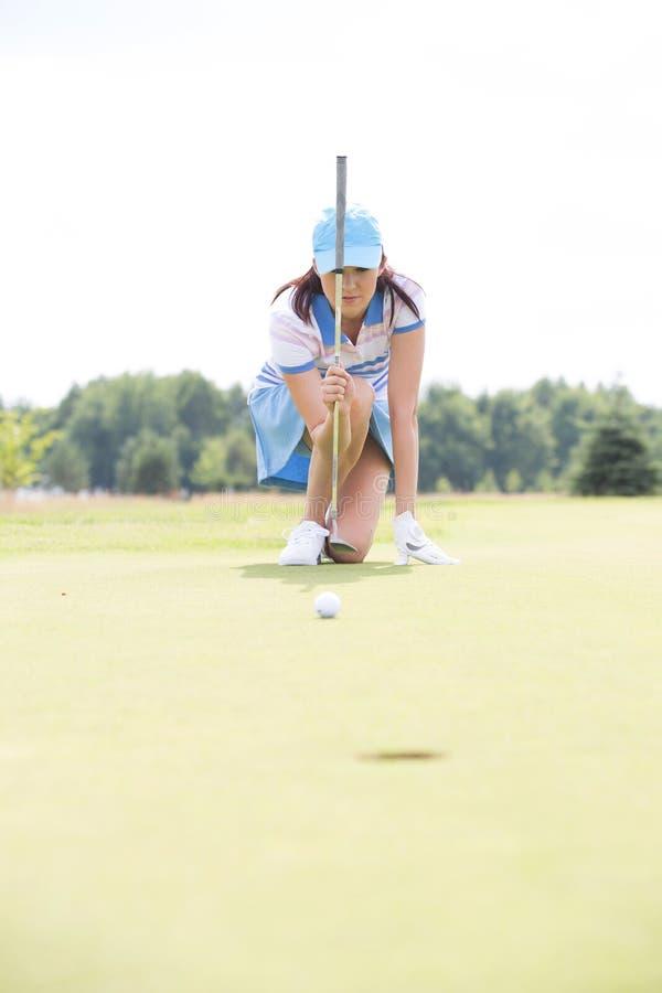Giovane donna che tende palla mentre inginocchiandosi al campo da golf immagini stock libere da diritti