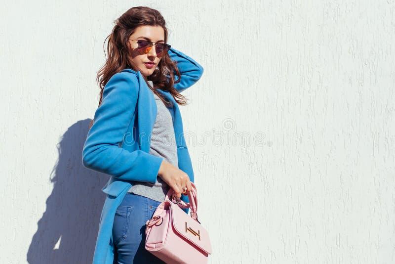 Giovane donna che tiene borsa alla moda e che porta cappotto blu d'avanguardia Vestiti ed accessori femminili della primavera Mod fotografia stock libera da diritti