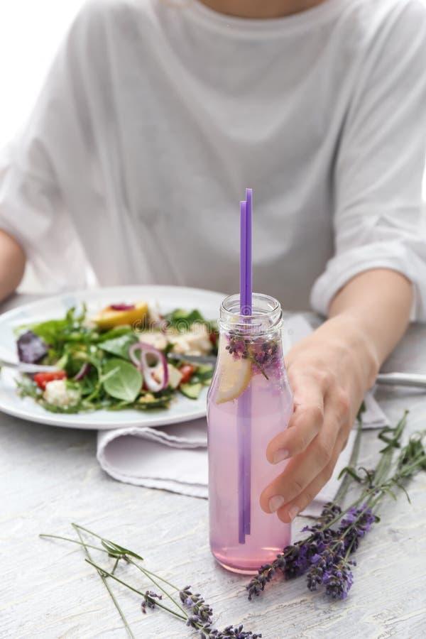 Giovane donna che tiene bottiglia di vetro della limonata della lavanda mentre mangiando insalata di verdure alla tavola, primo p immagine stock