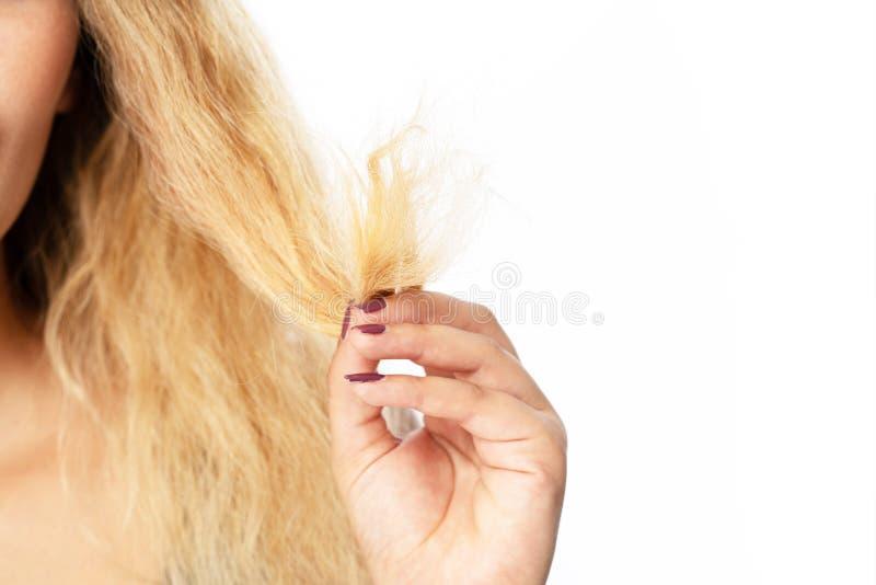 Giovane donna che tiene i capelli, decide di acconciarli immagini stock