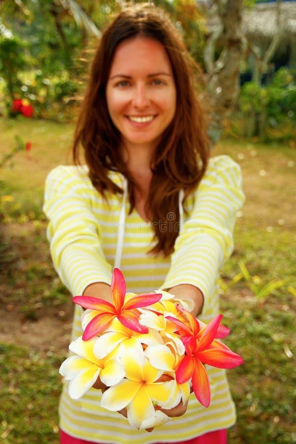 Giovane donna che tiene i fiori bianchi e rosa di plumeria fotografie stock libere da diritti