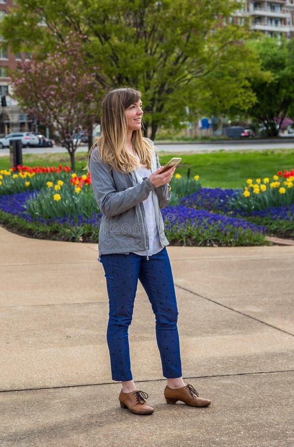 Giovane donna che tiene il suo telefono in un parco fotografia stock