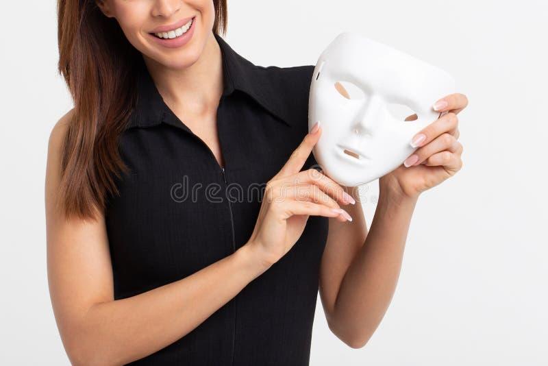 Giovane donna che tiene maschera bianca su fondo bianco fotografia stock