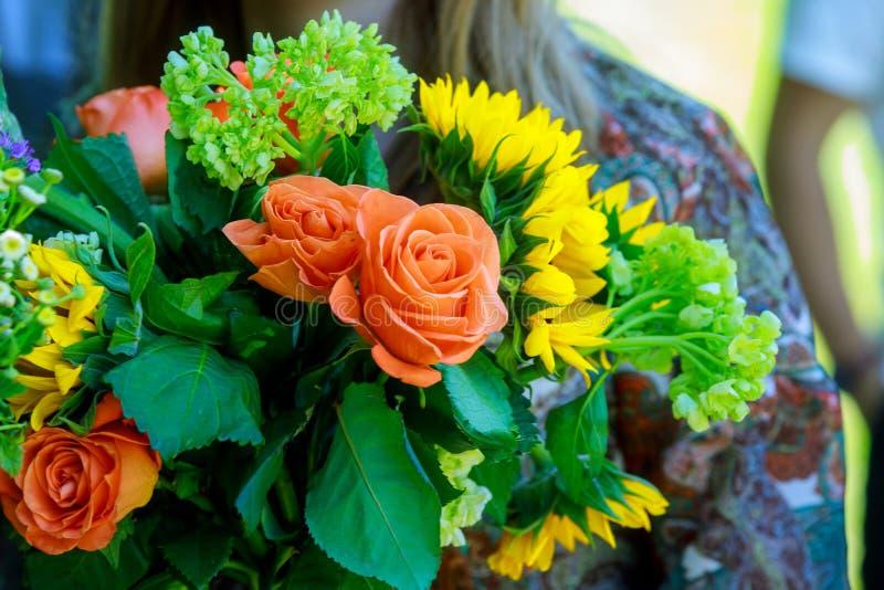 Giovane donna che tiene mazzo asimmetrico moderno dei fiori sulla via vicino al negozio di fiore fotografia stock