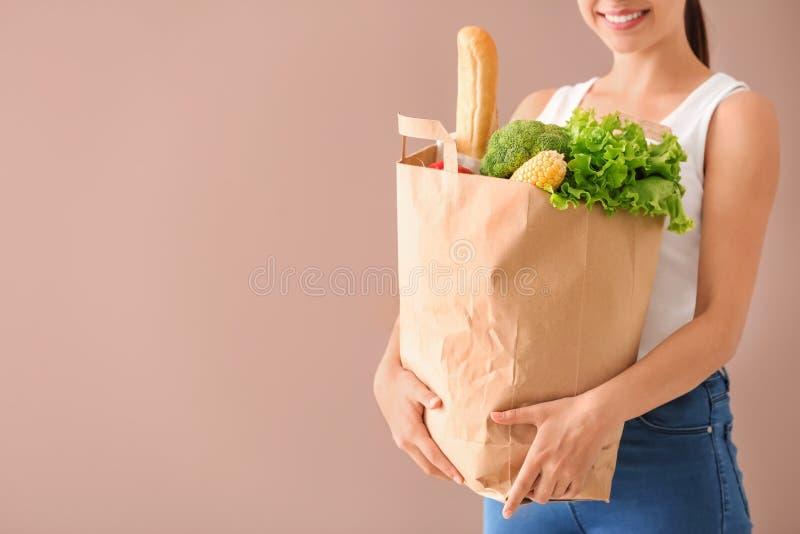 Giovane donna che tiene sacco di carta con i prodotti freschi sul fondo di colore Servizio di distribuzione dell'alimento immagini stock