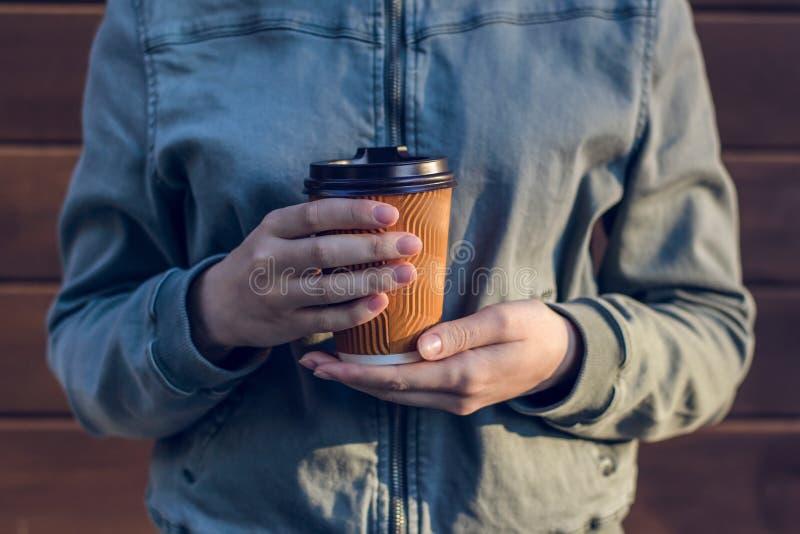 Giovane donna che tiene tazza del caffè fresco di mattina contro il takeaway di legno della persona della gente di tempo libero d fotografia stock