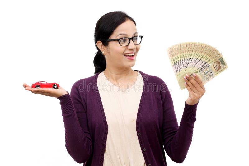 Giovane donna che tiene un'automobile del giocattolo e una valuta indiana immagine stock libera da diritti