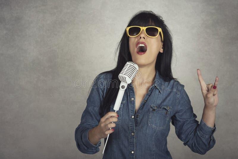 Giovane donna che tiene un canto del microfono immagini stock libere da diritti