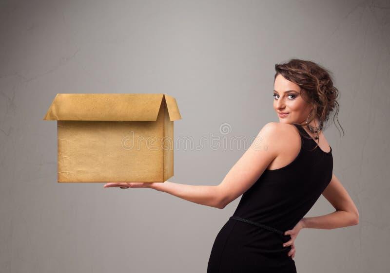 Giovane donna che tiene una scatola di cartone vuota fotografia stock