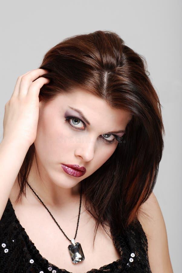 Giovane donna che tira la parte posteriore dei capelli fotografie stock libere da diritti