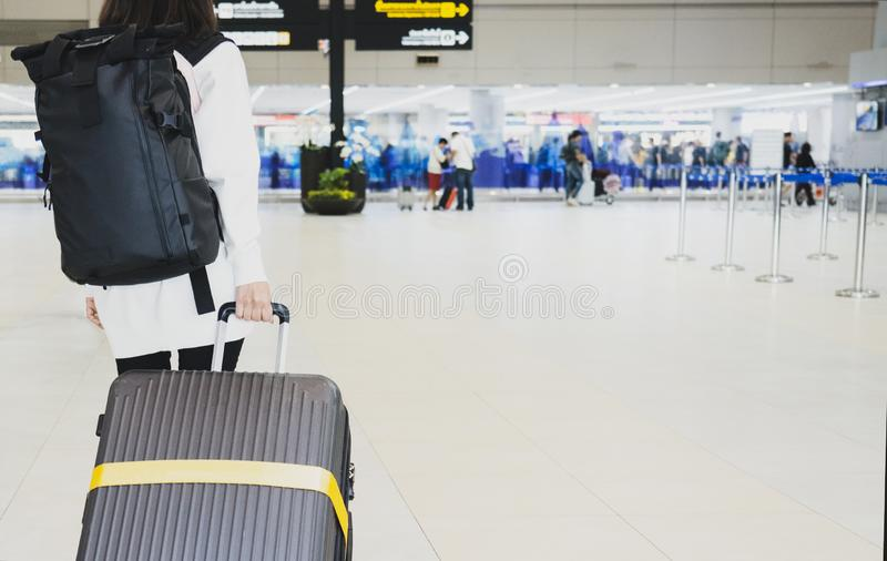 Giovane donna che tira valigia in terminale di aeroporto Viaggiatore della giovane donna in aeroporto internazionale con la valig fotografia stock