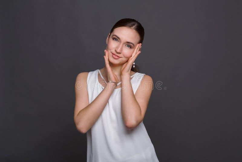 Giovane donna che tocca il suo fronte immagini stock libere da diritti
