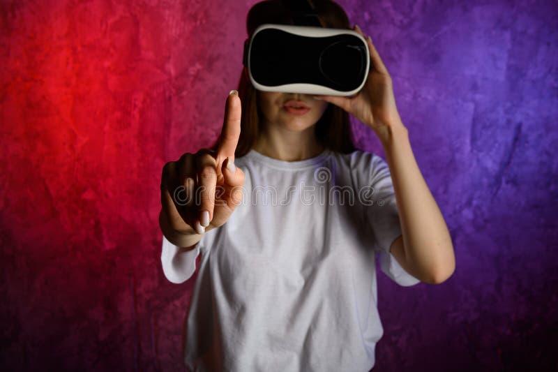 Giovane donna che tocca l'aria durante l'esperienza di VR Priorit? bassa blu e rossa fotografia stock libera da diritti