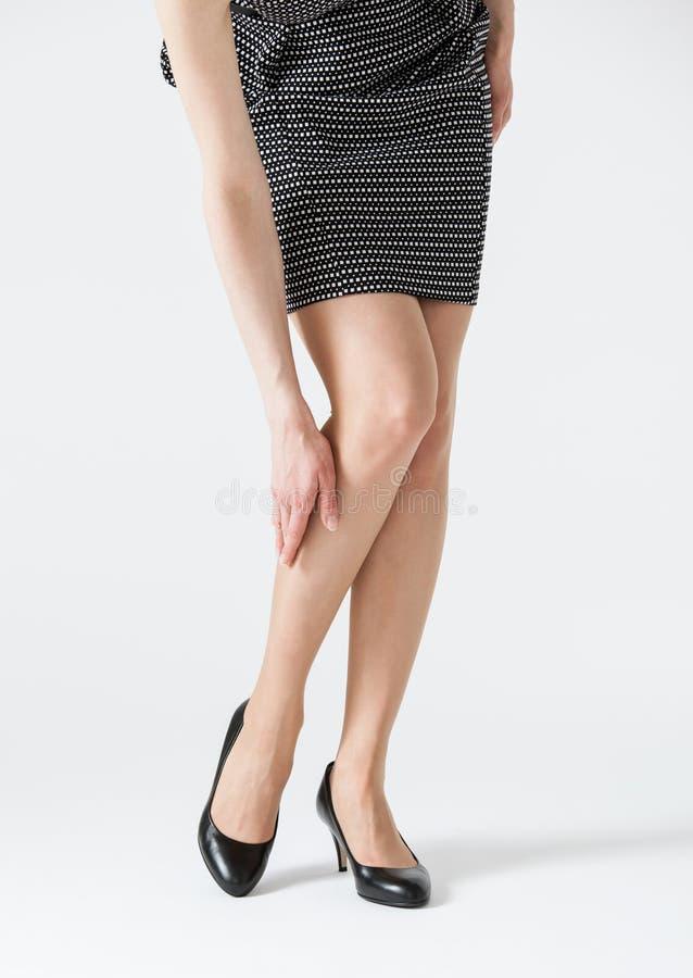 Giovane donna che tocca la sua gamba fotografie stock
