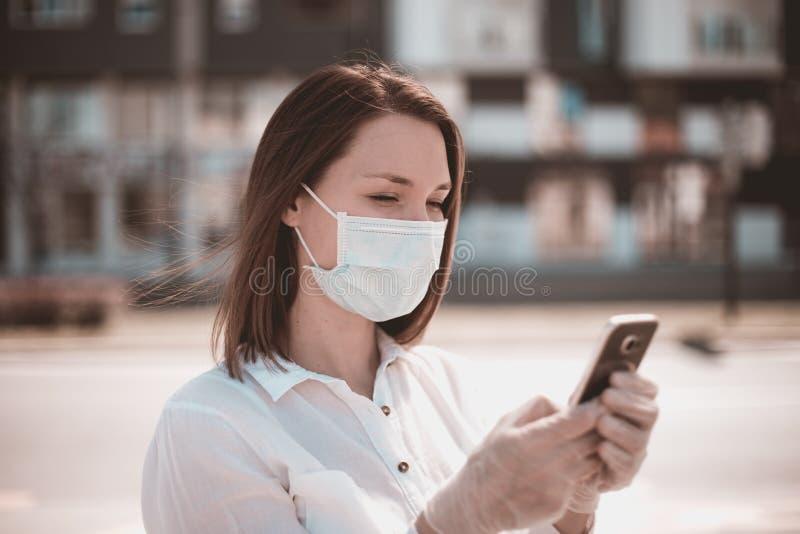 Giovane donna che usa smartphone in città indossa mascherina e guanti da protezione per virus coronavirus covid 19 immagine stock libera da diritti