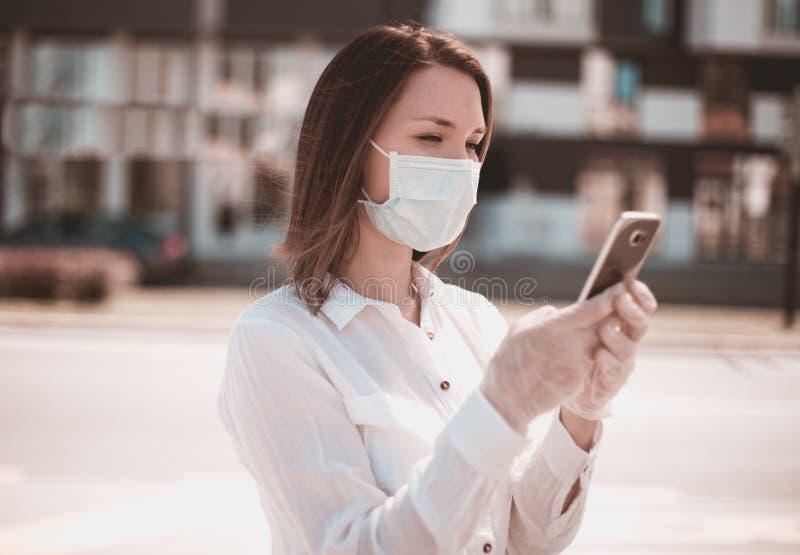 Giovane donna che usa smartphone in città indossa mascherina e guanti da protezione per virus coronavirus covid 19 immagine stock