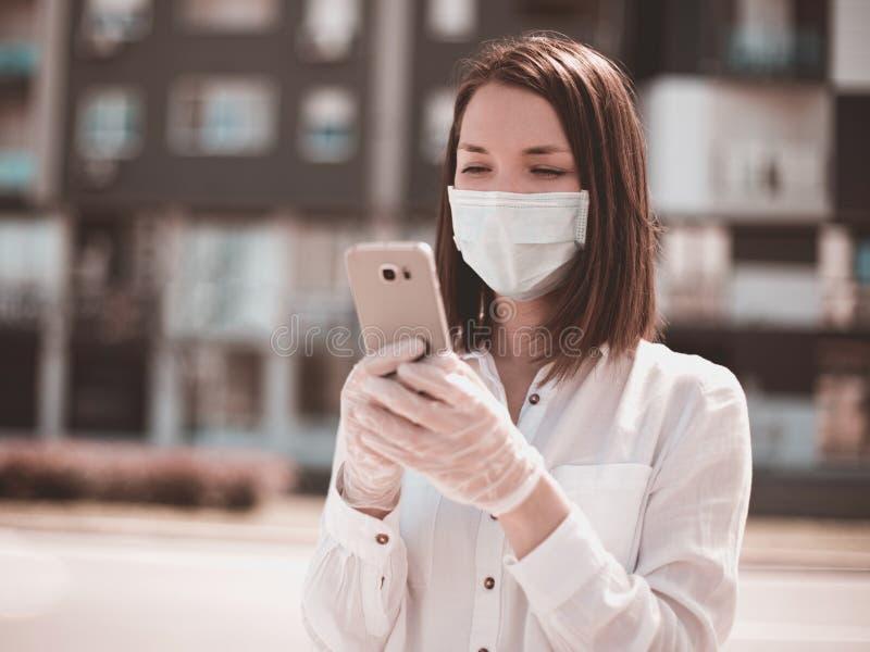 Giovane donna che usa smartphone in città indossa mascherina e guanti da protezione per virus coronavirus covid 19 fotografia stock libera da diritti