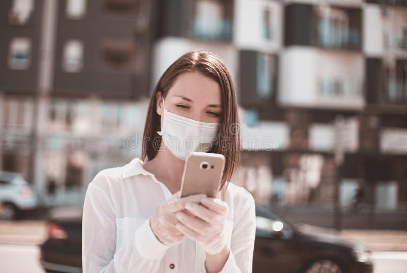 Giovane donna che usa smartphone in città indossa mascherina e guanti da protezione per virus coronavirus covid 19 fotografie stock libere da diritti