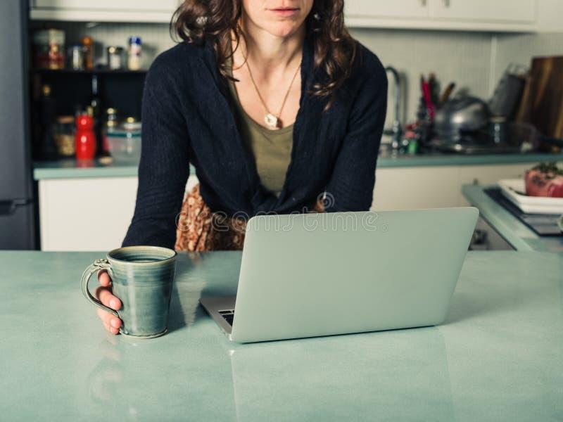 Giovane donna che utilizza computer portatile nella cucina fotografia stock