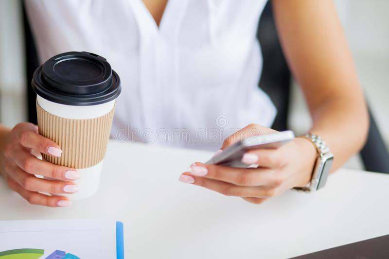 Giovane donna che utilizza il suoi telefono e caffè della bevanda nell'ufficio fotografia stock libera da diritti