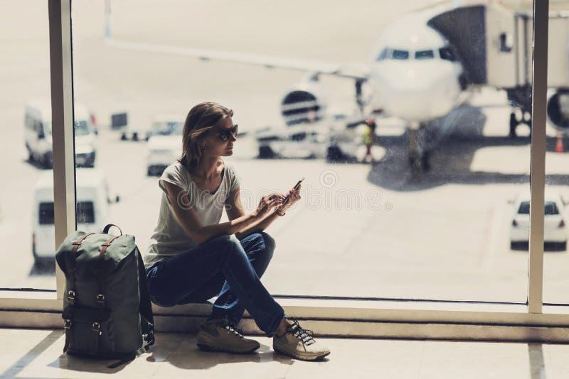 Giovane donna che utilizza smartphone nell'aeroporto, nel viaggio, nelle vacanze e nel concetto attivo di stile di vita immagine stock