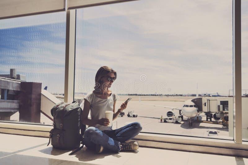 Giovane donna che utilizza smartphone nell'aeroporto, nel viaggio, nelle vacanze e nel concetto attivo di stile di vita fotografia stock