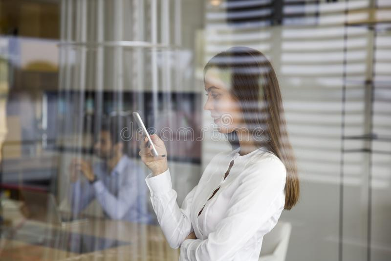 Giovane donna che utilizza telefono cellulare dietro il vetro nell'ufficio fotografie stock libere da diritti