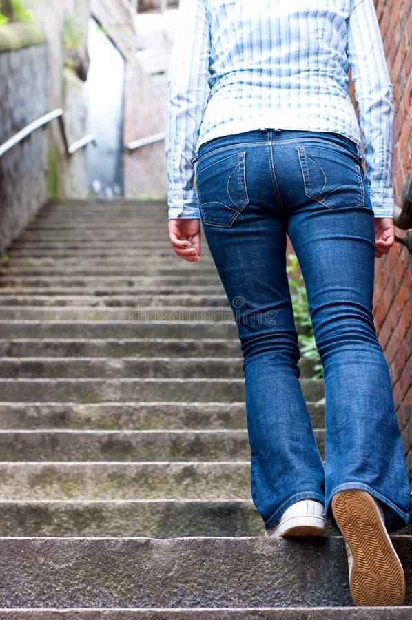 Giovane donna che va in su le scale immagini stock libere da diritti