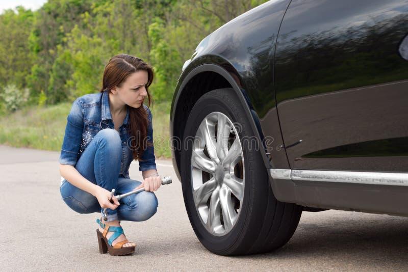 Giovane donna che verifica una gomma a terra sulla sua automobile fotografia stock libera da diritti