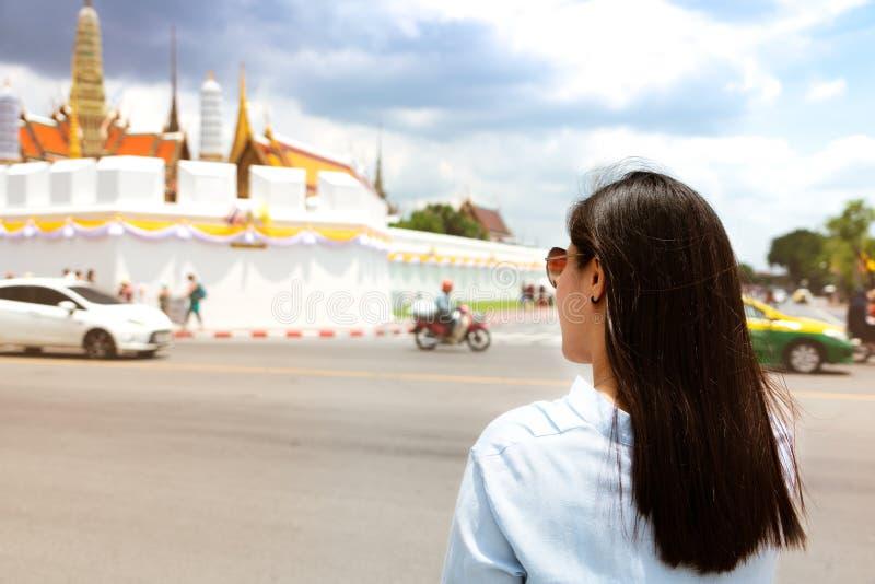 Giovane donna che viaggia al grandi palazzo e Wat Phra Keaw al tramonto a Bangkok, Tailandia fotografia stock libera da diritti