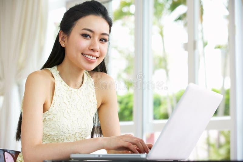 Giovane donna cinese che per mezzo del computer portatile nel paese fotografie stock libere da diritti