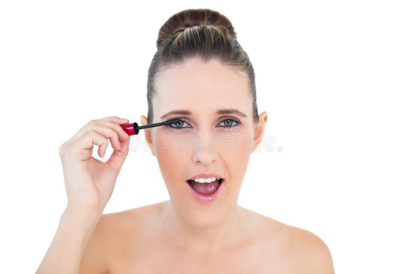Giovane donna colpita che applica mascara fotografie stock